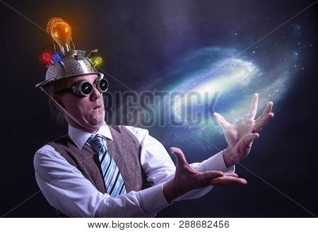 Distraught Looking Conspiracy Believer In Suit With Aluminum Foil Head Holding The Galaxy Or Univers