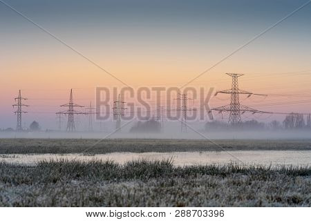 High Voltage Electrical Pole. Electric Powerline In The Nature. Morning Fog Under The Sunrise Sky.