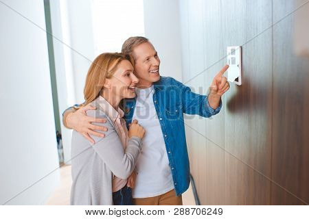 Happy Man Pointing At Smart Home Control Panel While Hugging Wife