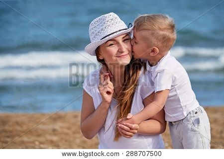 Happy Family At Sea Summer. Little Boy Son Hugs And Kisses Mother. Child Loves Mom. Portrait Young W
