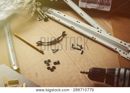 Tools For The Assembly Of Furniture, Furniture Details, Wrapping Film, Screws On A Sheet Of Cardboar