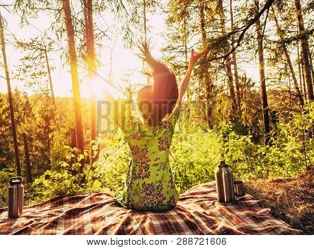 poster of Beautiful young girl with open arms sitting on a plaid in a forest glade during sunset bright sunlight around beauty of nature. Next to the girl is an iron thermos with cups. Unity with nature concept. Girl enjoying in the nature with arms up. Happy young