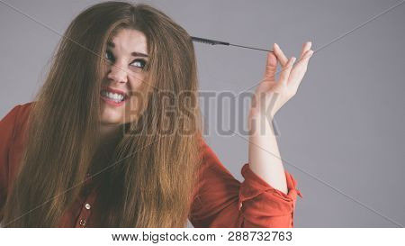 Funny teenage woman having problem with tangled tousled hair. Haircare problems concept. poster