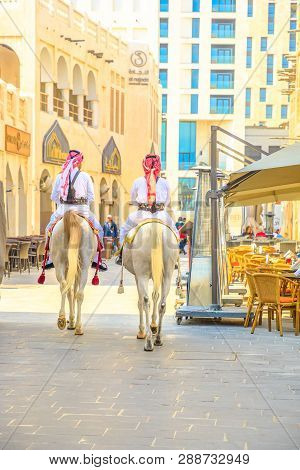 Doha, Qatar - February 20, 2019: Two Police On Horse In Traditional Clothes At Old Souq Waqif Riding