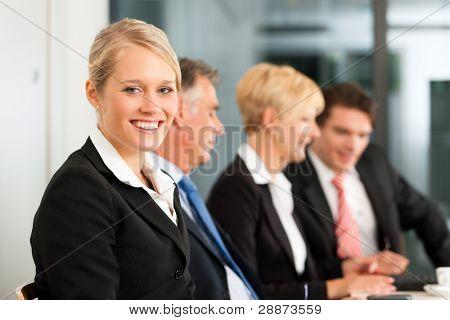 Business - Team in einem Büro; eine Frau schaut in die Kamera