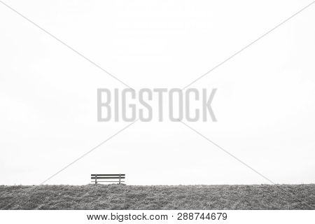 A Single Empty Wooden Bench On The Horizon Above A Grass Field Against A Large Grey Clouded Sky Depi
