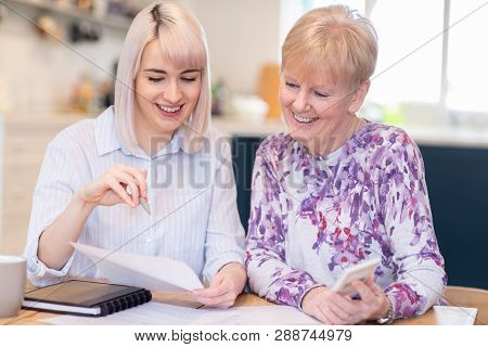 Financial Advisor Helping Senior Neighbor With Paperwork