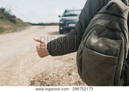Close-up Of A Man Hiker With A Backpack Hitch-hiking. He Raised His Finger Up And Tried To Stop The