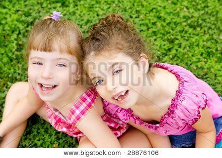 children girls laughing sitting on green grass park