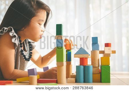 Little Girl In A Colorful Shirt Playing With Construction Toy Blocks Building A Tower . Kids Playing