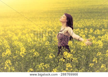Happy beautiful woman in free summer love of youth wellbeing. Attractive young beauty girl enjoying the warm sunny sun in nature rapeseed field takes time feeling sustainability and contemplation. poster