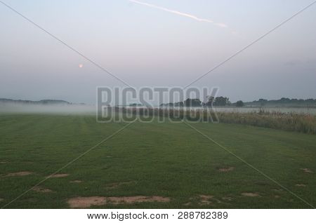 Fog On A Grass Field. The Grass Field Is Placed Near The River The Morning Fog Is Often Here