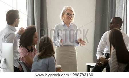 Old Woman Mentor Coach Training Multicultural Interns Group In Office