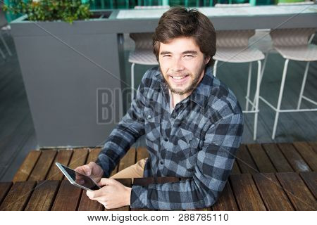 Delighted Young Man In Casual Shirt Using Tablet In Street Coffee Shop And Smiling At Camera Cheerfu