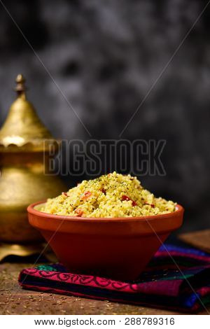 an earthenware bowl with tabbouleh, a typical levantine arab salad, on a table set for lunch or dinner, next to a golden teapot, against a dark gray background with some blank space on top