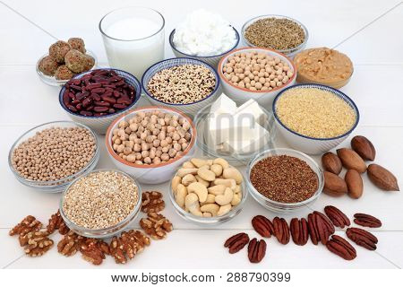 Vegan health food selection with bean curd, legumes, nuts, seeds, quinoa vegetable balls, cereals, almond milk, butter and yoghurt. Super foods high in antioxidants, dietary fibre, omega 3 & vitamins.