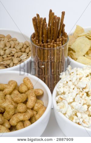 At parties and in television snacks may not be missing chips peanuts popcorn salted sticks poster