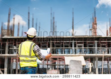 Engineering Consulting People On Construction Site Holding Blueprint In His Hand. Building  Inspecto
