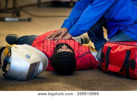 First Aid Training In The Factory Industrial. Welder Accident In Works And Fainting In A Factory Ind