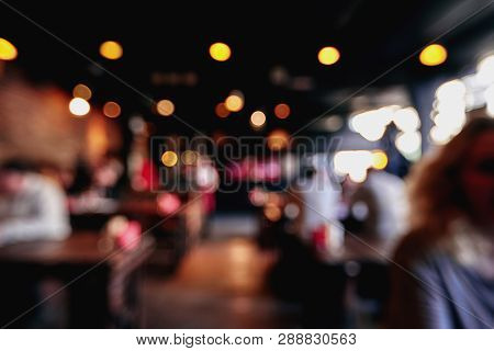 Blurred Restaurant Or Cafe Background. Tables And Chairs In The Lobby Of The Mall. Visitors To The R