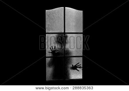 Dark Silhouette Of Girl Behind Glass. Locked Alone In Room Behind Door On Halloween In Grayscale. Ni