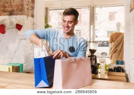 Man Packs Purchases In Paper Shopping Bag