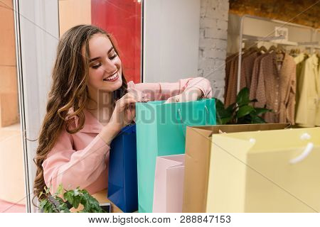Attractive Girl With Colorful Paper Shopping Bags In Store.
