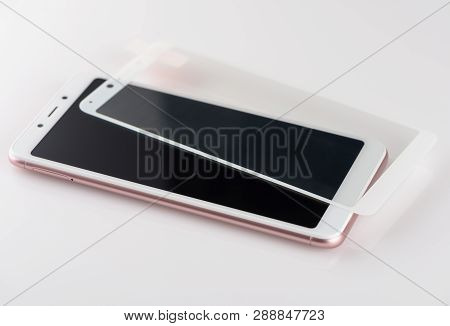 White  Smartphone And Protective Glass On It On A White Background.