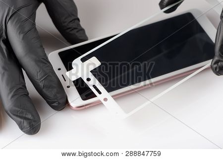 A Man Is Installing A Protective Glass On The Screen Of A Smartphone.