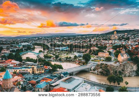 Evening View Of Tbilisi At Colorful Sunset, Georgia. Summer Cityscape. On Photograph Visible The Bri