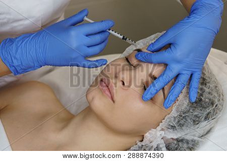 poster of Aesthetic cosmetology. Facelift in spa salon. Beautician makes injections girl in eyebrows. Smoothing of mimic wrinkles.