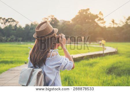 Young Woman Traveler Taking A Photo At Beautiful Green Paddy Field