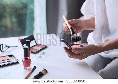 Young Woman Sitting On Sofa And Doing Makeup At Home