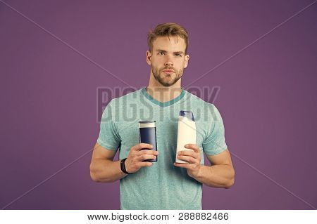 Make Your Choice. Man Stylish Hairstyle Holds Two Bottles Hygienic Product Violet Background. More N