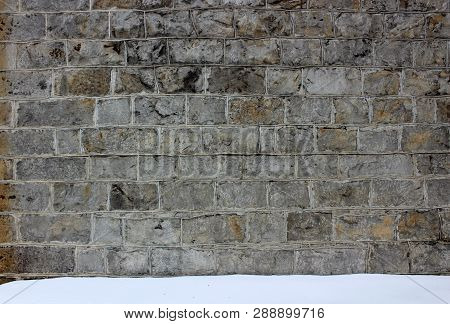 Large background of stone wall with gray color and rough surface that shows off the craftsmanship of builder, freshly fallen snow at base of it. poster