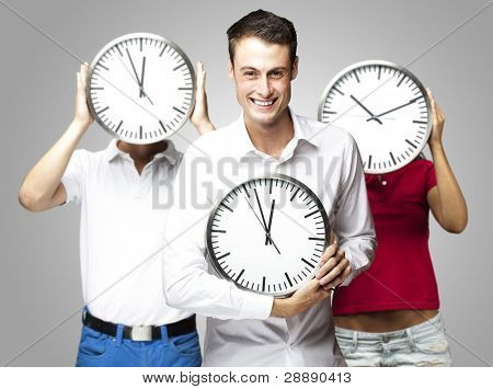 group of young students holding clock against a grey background