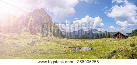 Idyllic Mountain Landscape In The Alps: Mountain Chalet, Meadows And Blue Sky