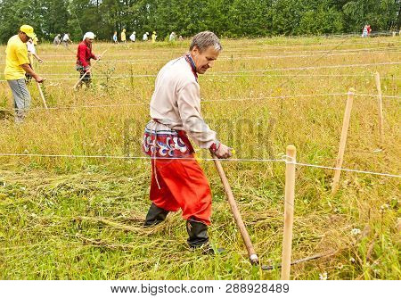 Mikhailovsk, Russia - 07/15/2018: Mow The Grass By Hand. Summer, Haymaking. Haymaker. Mowing Grass I