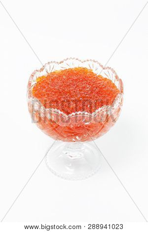 Red caviar in glass bowl isolated on white background