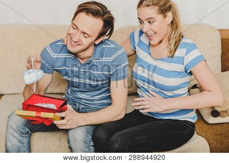 Woman giving man box with baby shoes, telling she is pregnant.