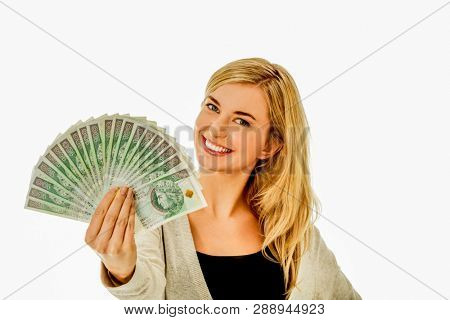 Smiling blond woman is holding fan with polish zlote banknotes.