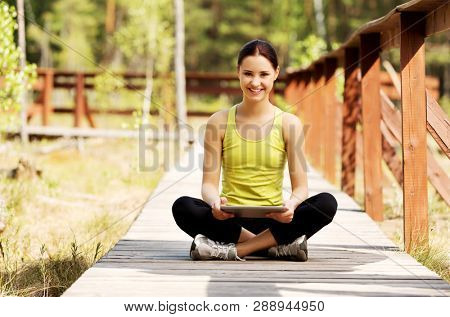 Teenage girl using tablet while sitting on wooden bridge in park.