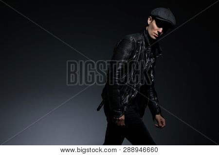 dramatic young man in leather jacket walks and leans forward while looking at the camera on grey background