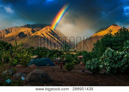 Rainbow over the mountains and tent set in the camping. Maui, Hawaii