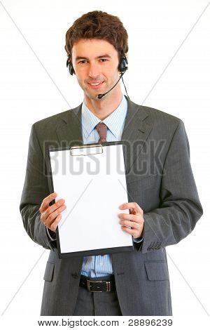 Smiling Modern Businessman In Headset Showing Blank Clipboard