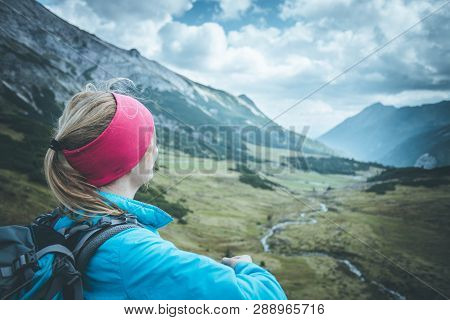 Female Blonde Mountain Climber With Backpack Is Enjoying The View