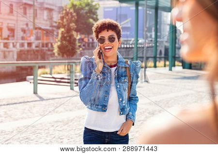 Cheerful young woman laughing while talking on mobile phone in the city centre. Excited brazilian girl walking while using smartphone. Happy african stylish girl enjoying while talking on cellphone.