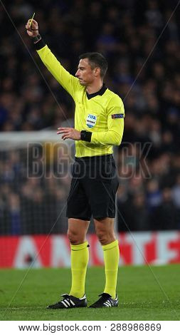 LONDON, ENGLAND - MARCH 7 2019: Referee Slavko Vicic shows a yellow card during the Europa League Round of 16, first leg match between Chelsea and Dynamo Kyiv at Stamford Bridge on March 7 2019