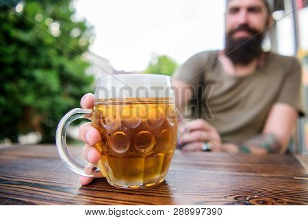 Craft beer is young, urban and fashionable. Distinct beer culture. Mug cold fresh beer on table close up. Man sit cafe terrace enjoying beer defocused. Alcohol and bar concept. Creative young brewer poster