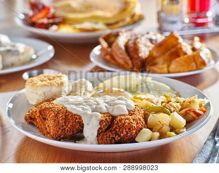 chicken fried steak covered in gravy with sunny side up eggs and breakfast foods at restaurant